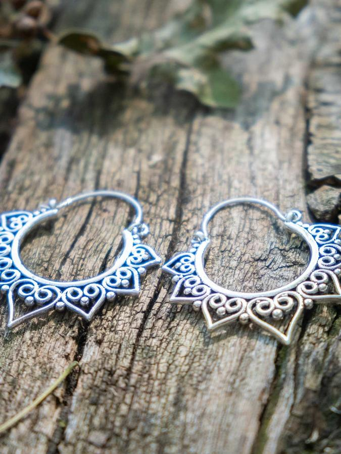 Round silver-plated earrings, with heart-shaped petals pattern and hook closure