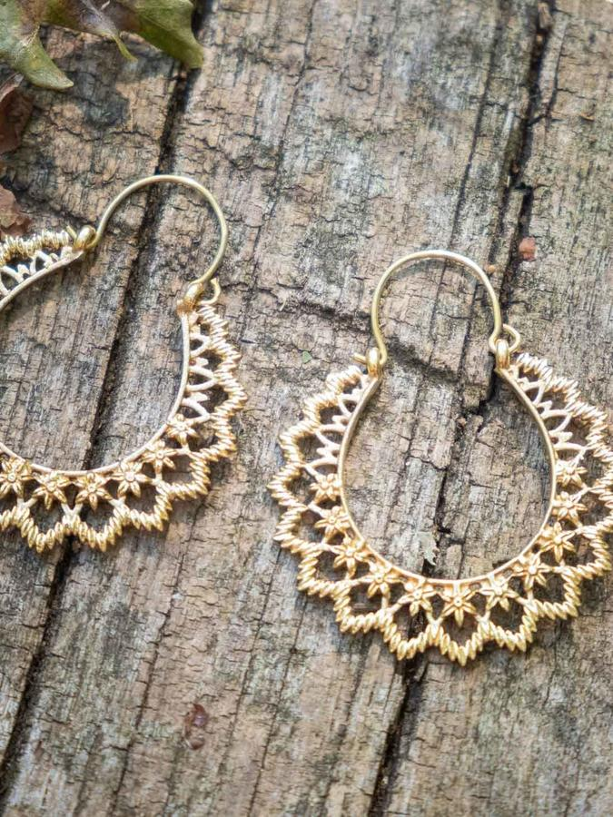 Oval brass earrings with flowers pattern and hook closure