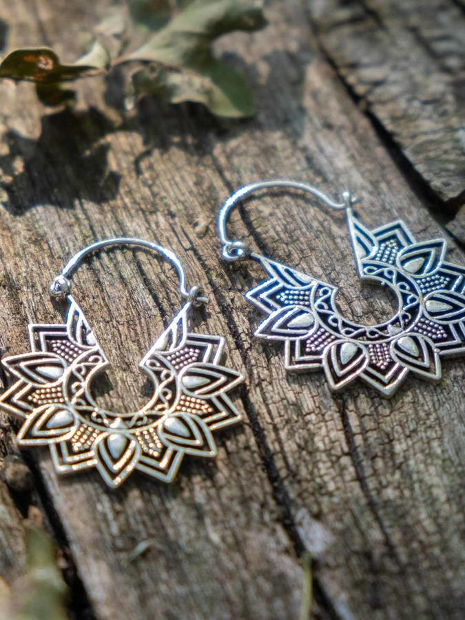 Round silver-plated earrings, with star petal pattern and hook closure