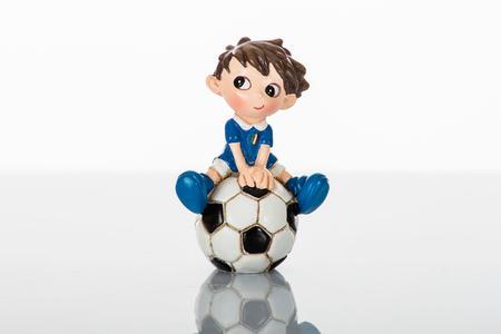 Calciatore in miniatura seduto sul pallone, due modelli assortiti , linea Cuore in Campo