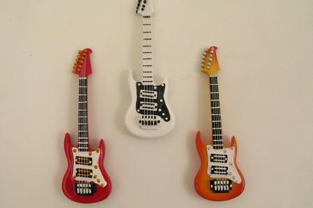 Chitarra elettrica piccola con magnete. tre colori assortiti: bianca, rossa e arancio, linea Cuorematto